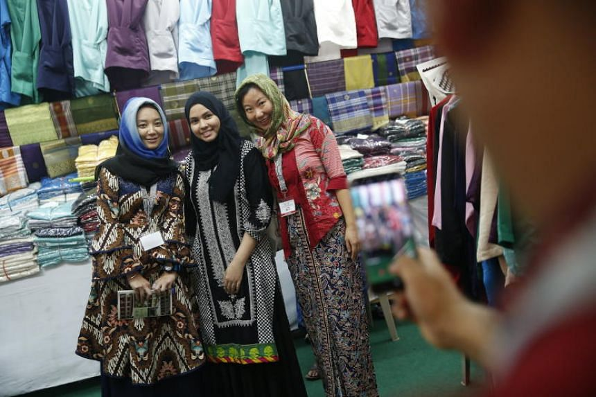 Participants in the Cultural Heritage Race posing for pictures with a stall holder during the event, on May 20, 2018.