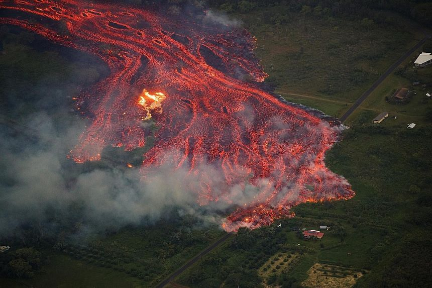An aerial view of a massive flow of fast-moving lava consuming everything in its path. The remnants of one home (left) can be seen burning on Saturday while the lava approaches another home in Pahoa, Hawaii.