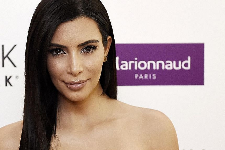 """Reality TV star Kim Kardashian West (left) was criticised for promoting unhealthy eating habits when she posted an image of herself with an """"appetite suppressant lollipop""""."""