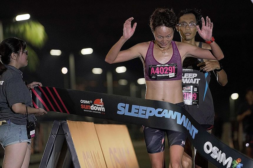 Hu Xiu Ying crossing the finish line of the Osim Sundown Marathon in 3:35:50 early yesterday morning. The 39-year-old China-born Singaporean, who took a 10-year break to look after her children, aims to compete in next year's SEA Games in the Philipp