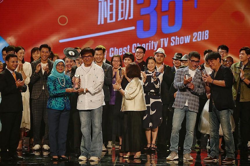 President Halimah Yacob presenting a Community Chest Enabler Award to actor Jackie Chan at the Community Chest Charity TV Show last night. Taiwan-based singer Wakin Chau (foreground, far right) and Taiwanese music producer and singer-songwriter Jonat