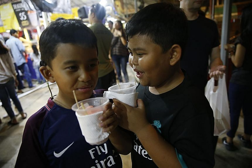 Mohammed Izwan Shah, nine, and his brother Mohammed Ilhan Shah, eight, trying the dragon's breath, a frozen dessert. Despite the increase in rental costs, many hawkers at the bazaar remain optimistic about sales this year.