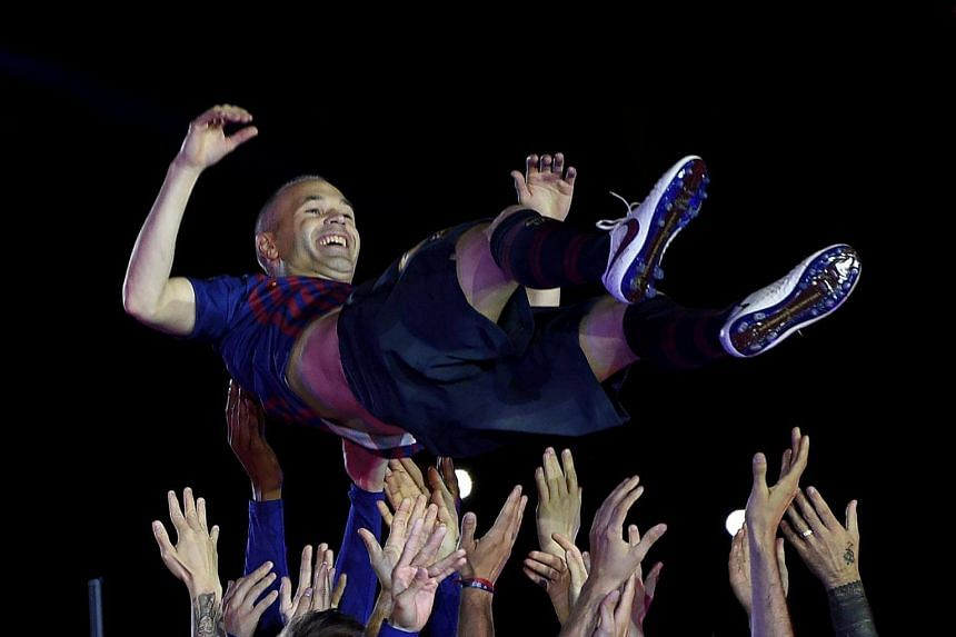 Barcelona's Spanish midfielder Andres Iniesta is thrown in the air by teammates during a tribue at the end of the Spanish league football match between FC Barcelona and Real Sociedad at the Camp Nou stadium in Barcelona on May 20, 2018.