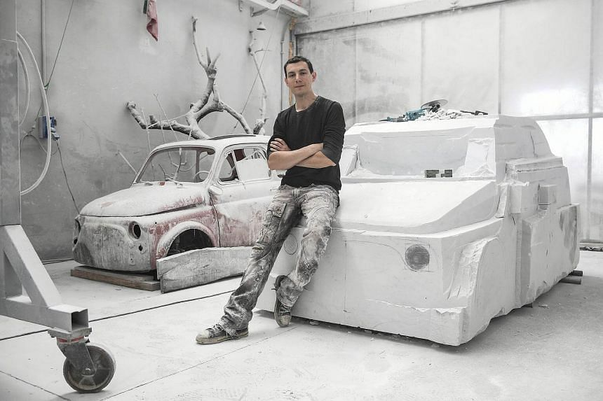 Italian artist Nazareno Biondo poses on his ongoing sculpture made with Carrara's marble representing the iconic car Fiat 500 in Cafasse, near Turin, on May 16, 2018.
