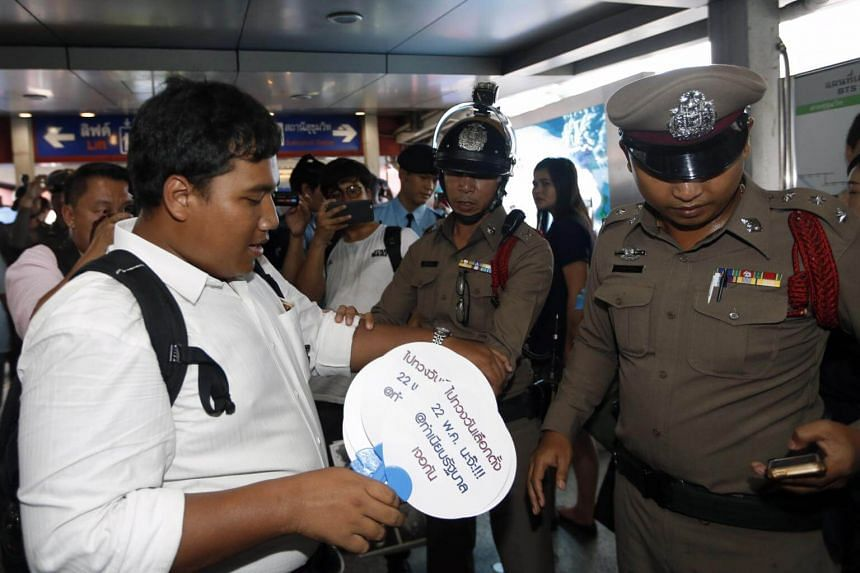 Police officers stopping a pro-democracy activist from handing out fans with caricatures of Thai Prime Minister Prayut Chan-o-cha during a rally calling for a general election outside a shopping mall in Bangkok, Thailand, on May 18 2018.