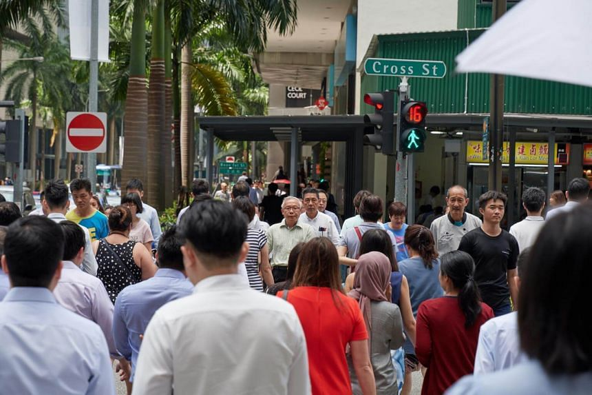 File photo showing pedestrians crossing the road during the lunch hour in Singapore's central business district.