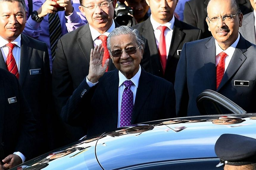 Prime Minister Mahathir Mohamad waves as he leaves after addressing his first assembly of civil servants from the Prime Minister's office in Putrajaya on May 21, 2018.