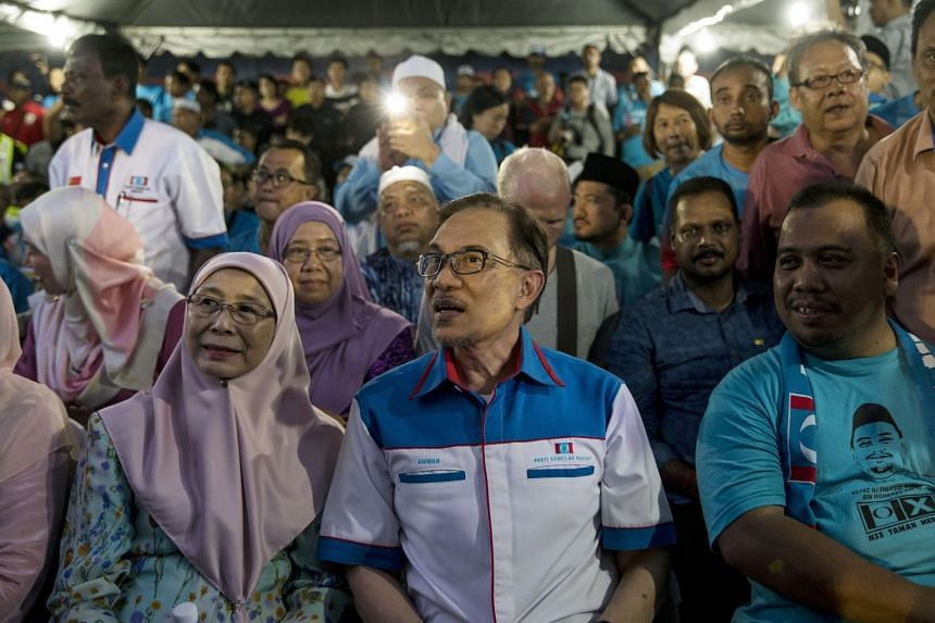 Mr Anwar Ibrahim (centre) sits with his wife Wan Azizah Wan Ismail, Malaysia's deputy prime minister, at a Pakatan Harapan alliance event in Petaling Jaya, Selangor, Malaysia, on May 16, 2018.