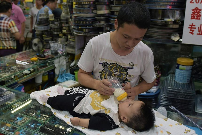 A father feeding his baby inside a shopping mall in Shenzhen, China on May 11, 2017.