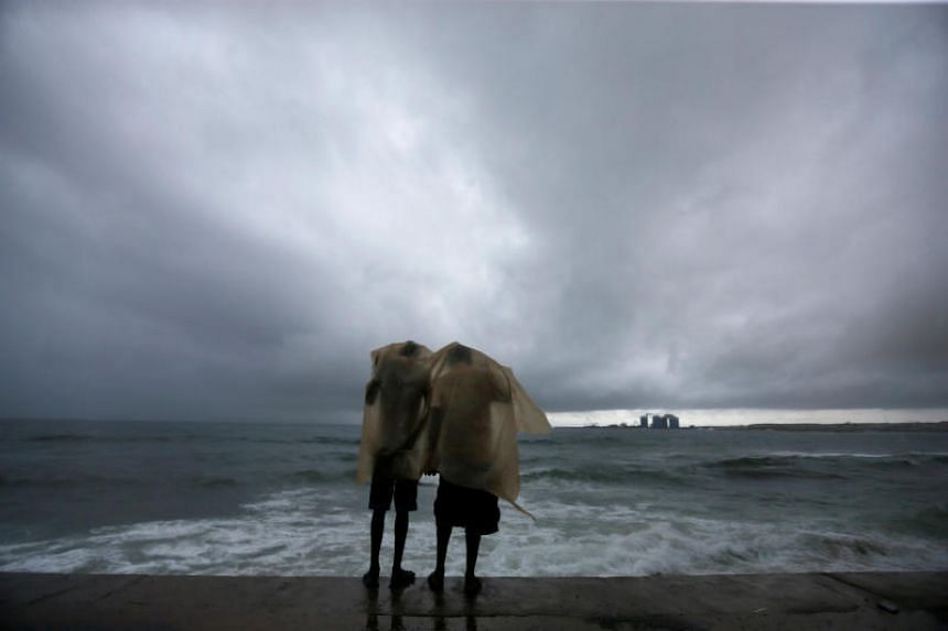 Two men using a plastic sheet to protect themselves from heavy rains as they stand by the sea in Colombo, Sri Lanka, on May 17, 2018.