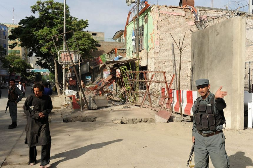 Afghan security officials inspect the scene a day after insurgents attacked police stations in Kabul on May 10, 2018.