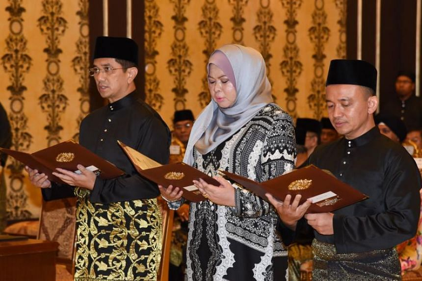 Minister of Economic Affairs Mohamed Azmin Ali, Minister of Rural Development Rina Harun and Minister of Education Maszlee Malik taking their oath during a swearing-in ceremony in front of Malaysia's King Muhammad V (unseen) at the National Palace in