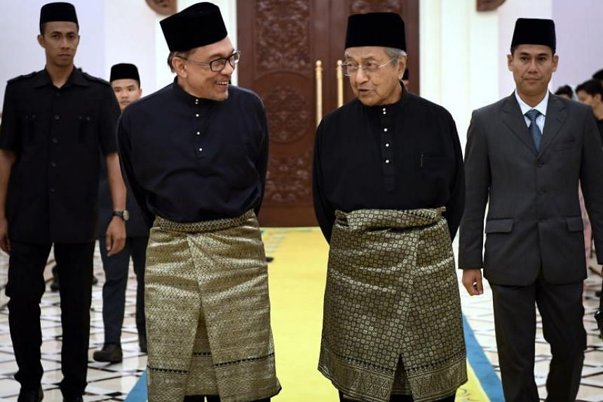 Malaysia's premier-in-waiting Anwar Ibrahim and Prime Minister Mahathir Mohamad at the royal palace.