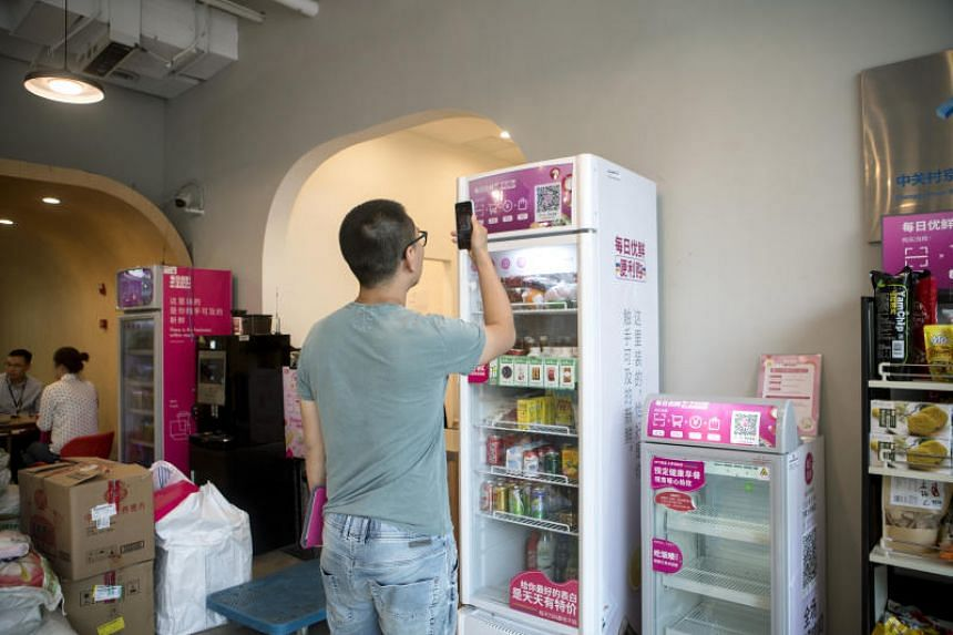 A customer scans a QR code using a smartphone to purchase products from a Mr Fresh unmanned kiosk inside the offices of its affiliate Miss Fresh in Beijing on May 9, 2018.