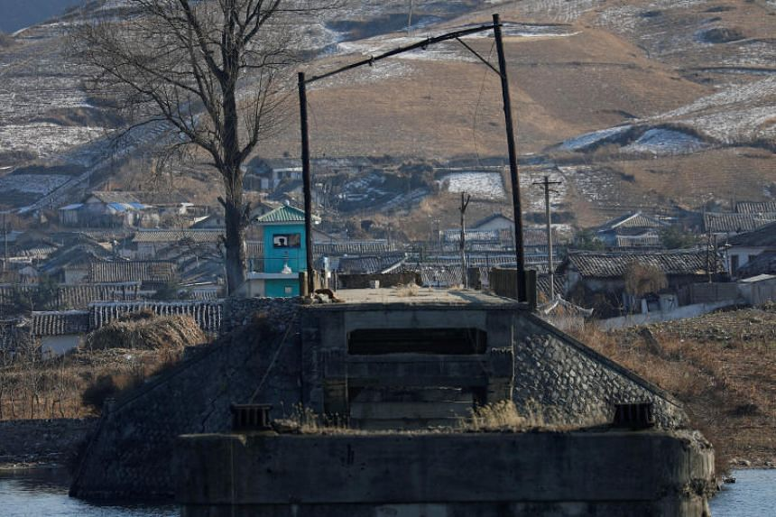 A North Korean border guard, as seen from the Chinese side of the border north of Dandong, China, takes position at Hekou's Broken Bridge over the Yalu River, north of the towns of Sinuiju in North Korea on Nov 20, 2017.