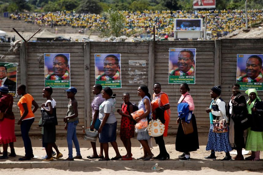 People queue to enter an election rally of Zimbabwean President Emmerson Mnangagwa's ruling ZANU PF party in Mutare on May 19, 2018.