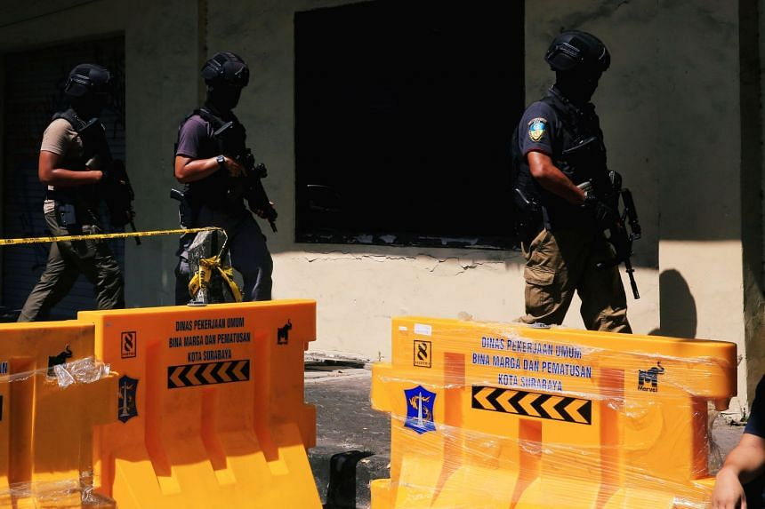 Anti-terror police patrol the street following a bomb blast at a police office in Surabaya.