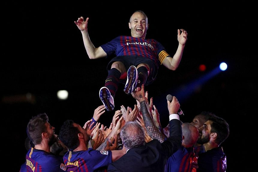 Left: Barcelona players toss Andres Iniesta into the air after a 1-0 win over Real Sociedad on Sunday, his last game in club colours. During the post-match ceremony, all the Barca players wore shirts with Iniesta's name. Below: Fernando Torres scored