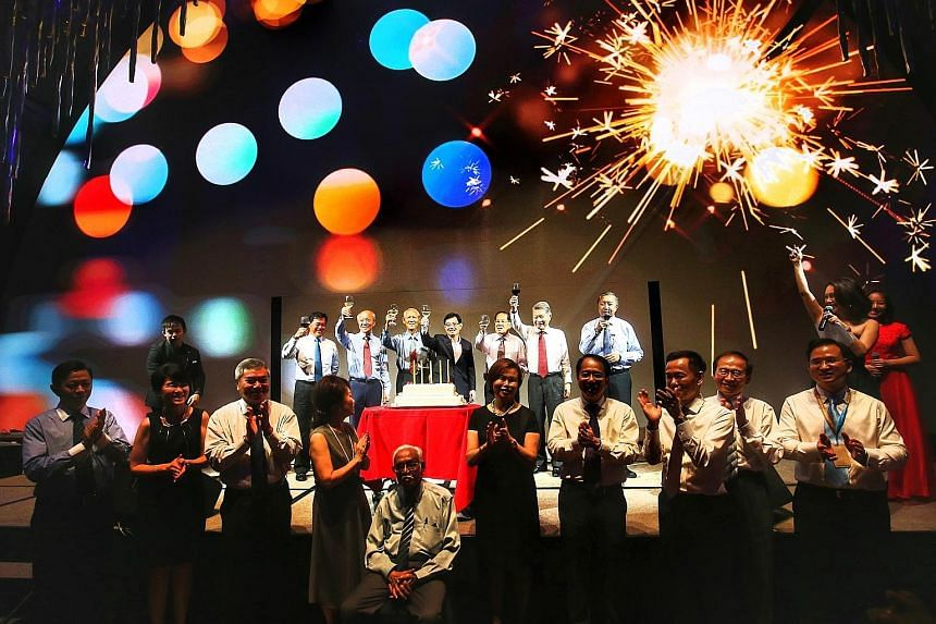 Mr Heng Swee Keat (centre, on stage) and other guests raising a toast to Singapore Pools during its golden jubilee celebration at JW Marriott Hotel yesterday.