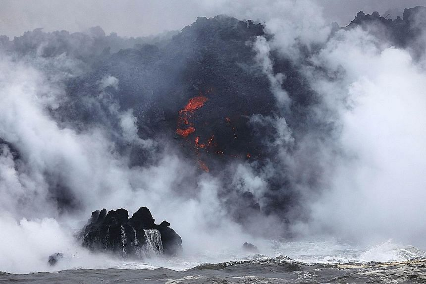 """A steam plume rising as lava (centre) enters the Pacific Ocean, after flowing to the water from a Kilauea volcano fissure, on Hawaii's Big Island on Sunday. Officials are concerned that """"laze"""", a potentially dangerous product formed when hot lava hit"""