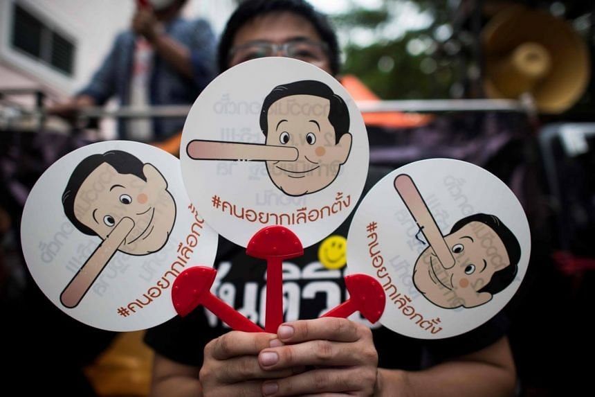 A protester displays placards with a caricatures of Thai Prime Minister Prayut Chan-O-Cha before a demonstration to mark the fourth year of junta rule in Bangkok on May 22, 2018.