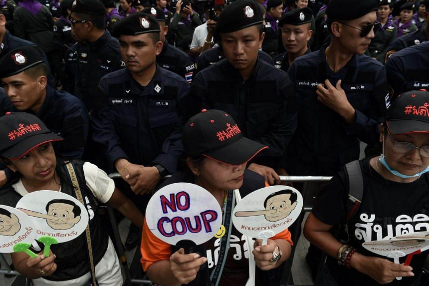 Demonstrators holding placards stand next to police barricade outside Thammasat University during a protest in Bangkok, on May 22, 2018.