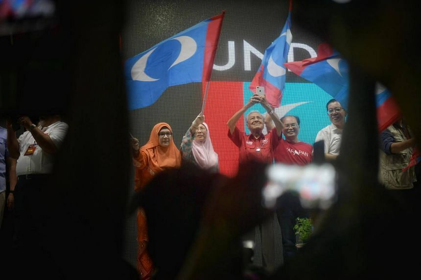 Malaysia's prime minister Mahathir Mohamad holding up a mobile phone at a Pakatan Harapan rally.