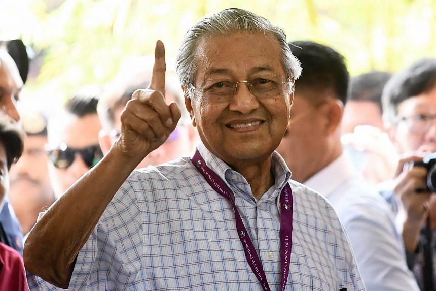 Dr Mahathir Mohamad gestures at a polling station during the 14th general election in Alor Setar, on May 9, 2018.