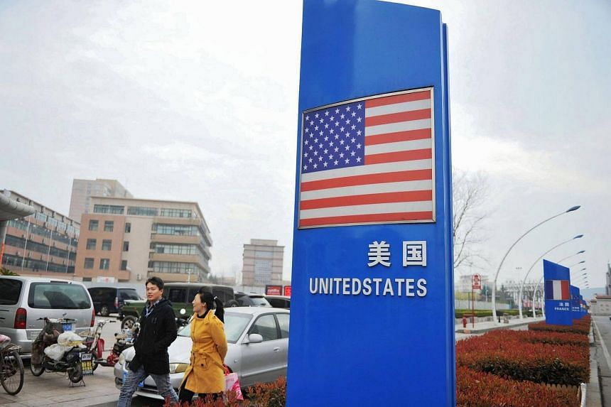 A sign with a US flag is seen outside a supermarket selling foreign goods in Qingdao, in China's eastern Shandong province, on April 5, 2018.