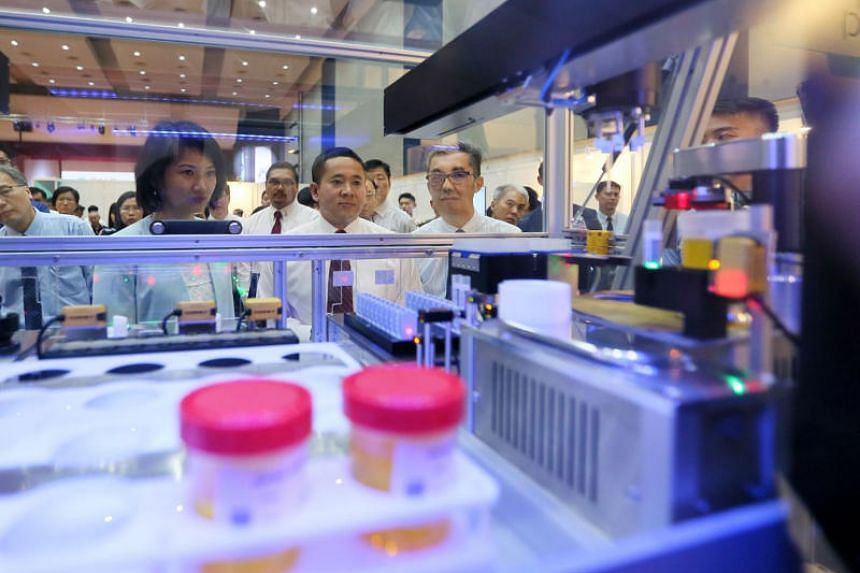 (From left) Ms Sun Xueling, Senior Parliamentary Secretary for Home Affairs and National Development, Mr Amrin Amin, Senior Parliamentary Secretary for Home Affairs and Health, and Mr Ng Ser Song, director, CNB, viewing the Specimen Handling Platform