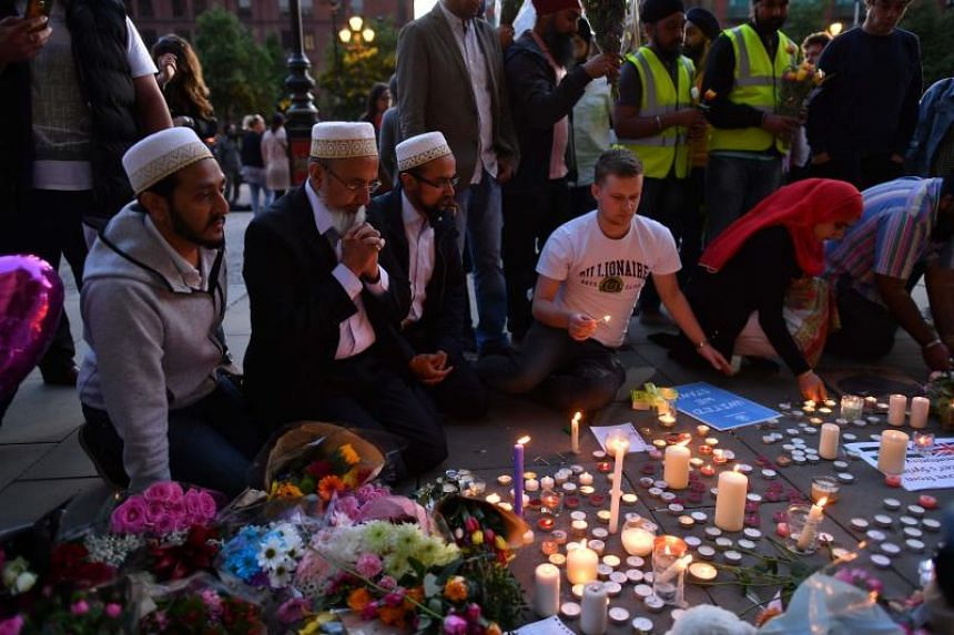 File photo showing people praying and lighting up candles at Albert Square in Manchester on May 23, 2017, following a terrorist attack at the Manchester Arena.