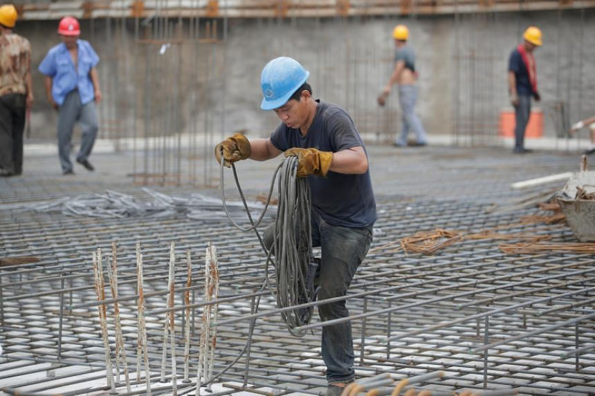 File photo showing a migrant worker from Baoding, Hebei province, laying a cable at a construction site in Beijing, China.