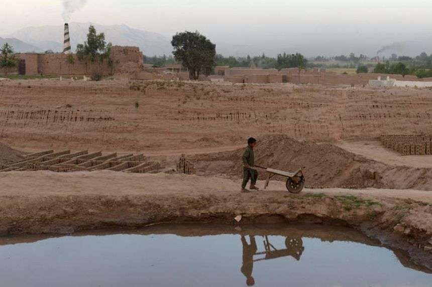 A file picture of an Afghan boy pushing a wheelbarrow on the outskirts of Jalalabad, Afghanistan.