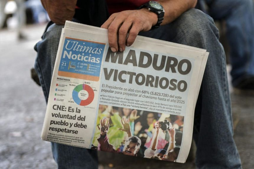 A man holds a newspaper referring to the victory of re-elected President Nicolas Maduro in the Venezuelan presidential election in Caracas, on May 21, 2018.
