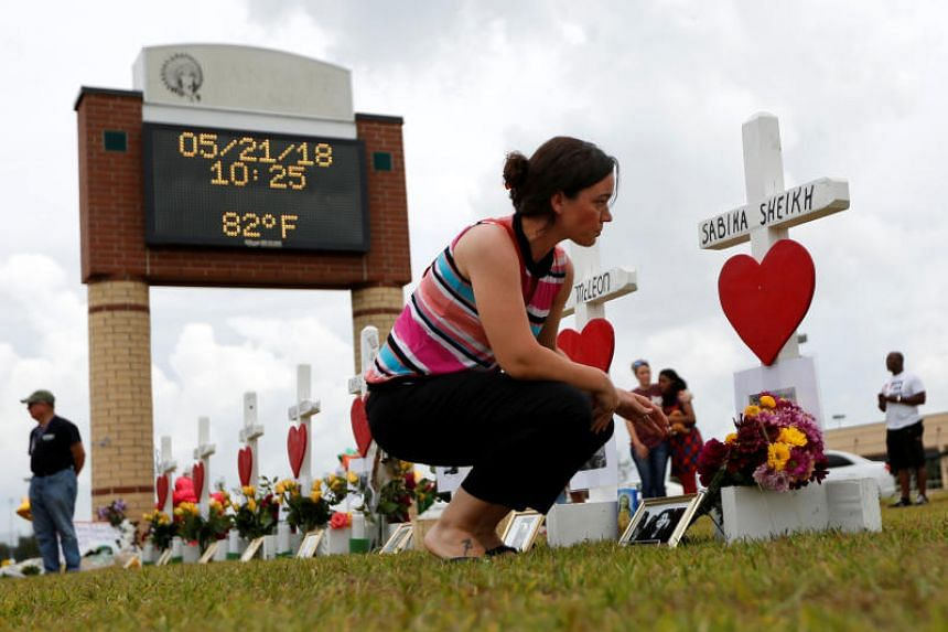 A woman prays at a makeshift memorial left in memory of the victims killed in a shooting at Santa Fe High School in Santa Fe, Texas, US on May 21, 2018.