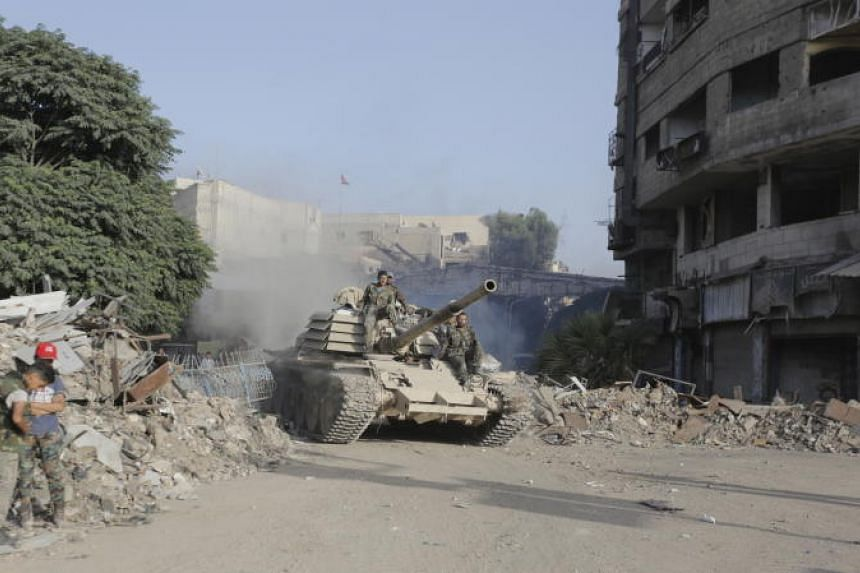 Soldiers ride atop a tank in destroyed parts of the Yarmouk camp neighborhood in south Damascus, Syria, on May 21, 2018.