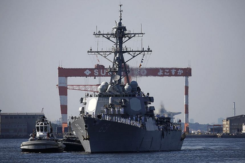 The USS Milius, one of the US Navy's most advanced guided missile destroyers, arriving in Japan yesterday. The show of force is a reminder of the military pressure that can be brought to bear on North Korea as the US presses it to abandon its nuclear