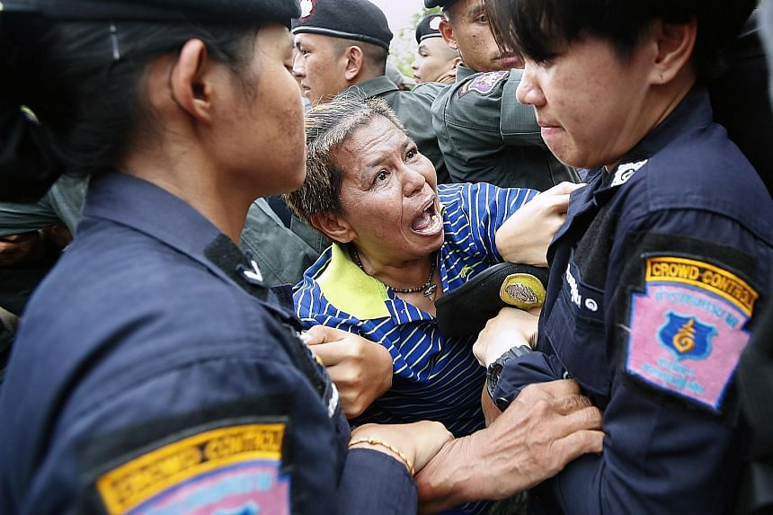 A protester being arrested by police near Government House in Bangkok yesterday. The group behind the march is calling for polls later this year, after the military government had repeatedly pushed back the general election after initially promising