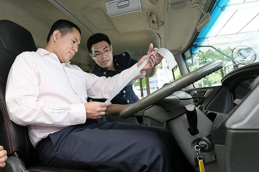 Senior Parliamentary Secretary for Health and Home Affairs Amrin Amin in a container truck equipped with a vehicle monitoring system. With him is Mr Alvin Pan of the Singapore Police Force.