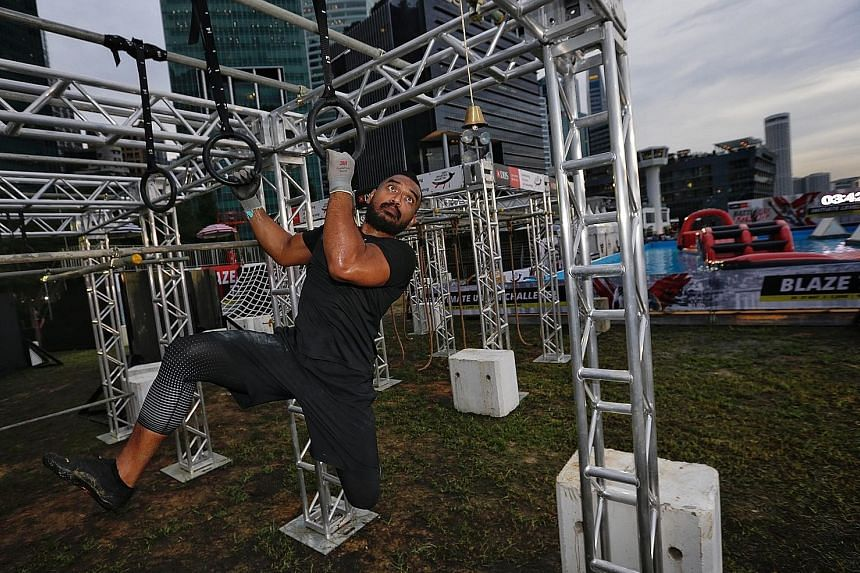 """Muhammad Ismail, 35-year-old master coach at Ritual Gym, negotiating an """"Insane"""" level obstacle course during a media preview of the DBS Marina Regatta yesterday."""