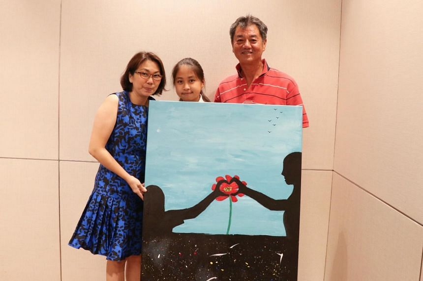 (From left) Marie Huang, Matilda Huang Yu Jing, Jimmy Khoo Eng Chew. Mr Khoo (right) bought the painting during the auction for $1,200 from the artists, Matilda and her mother Mrs Huang.