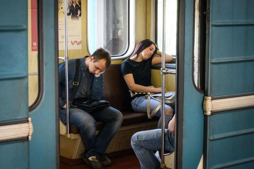 Commuters sleep in a metro car in Moscow, on May 23, 2018.
