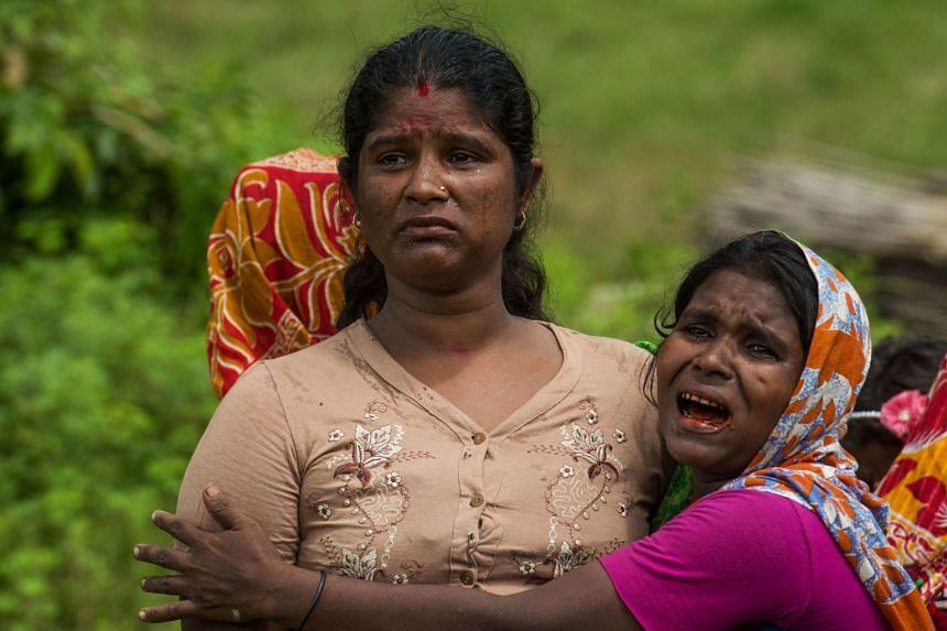 Hindu women cry near the dead bodies of their family members in Ye Baw Kyaw village in September 2017.