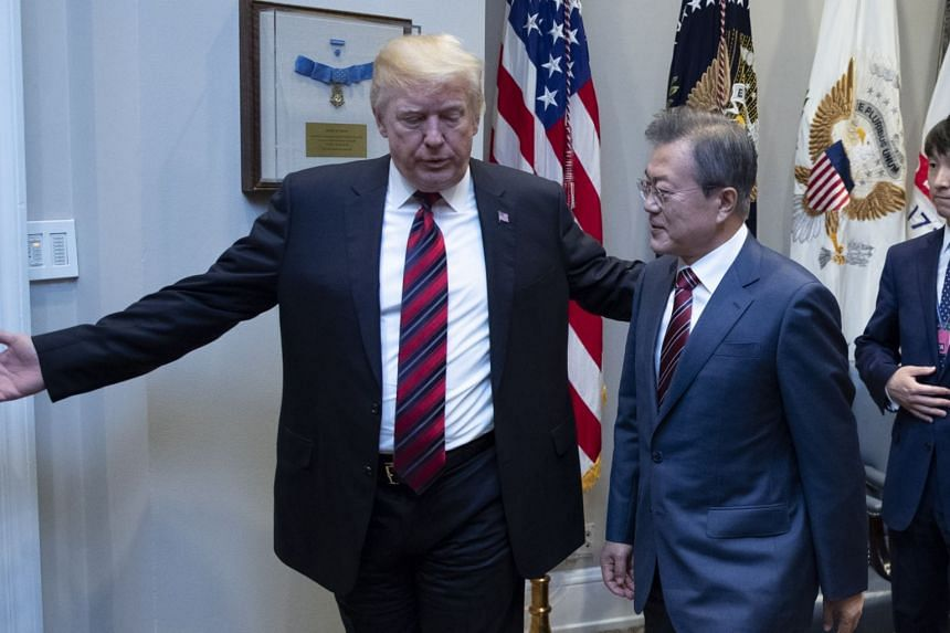 US President Donald Trump (left) guiding South Korean President Moon Jae In ahead of a meeting at the White House in Washington, DC, on May 22, 2018.