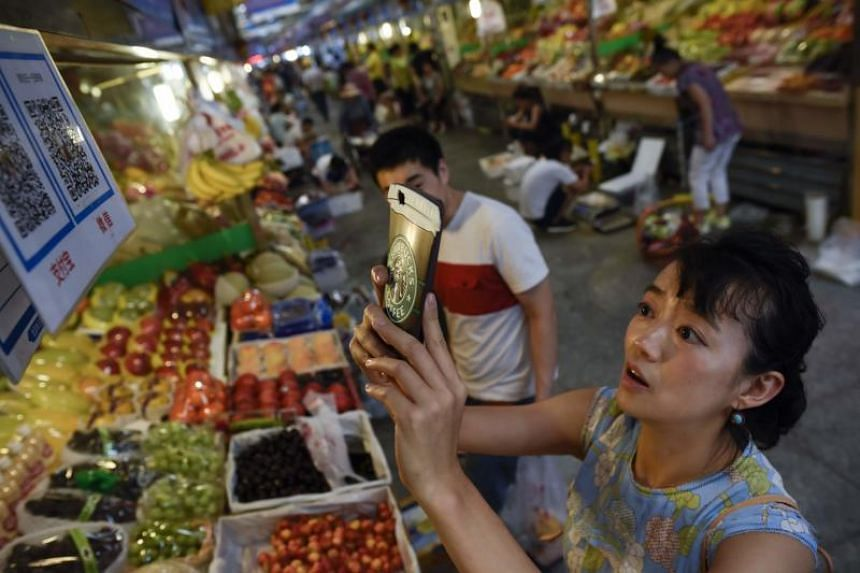 A woman making purchases by scanning QR codes using her smartphone at a fruit stall in a market in Beijing, China.