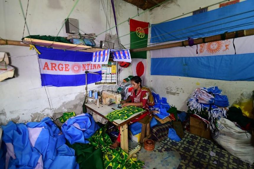 A Bangladeshi worker sewing flags for participating nations of the World Cup in Narayanganj, on the outskirts of Dhaka, on May 17, 2018.