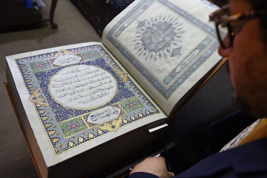 Afghan master miniature artist Mohammad Tamim Sahibzada shows a Quran made with silk fabric at the Turquoise Mountain Foundation in Mourad Khani, Kabul on April 19, 2018.