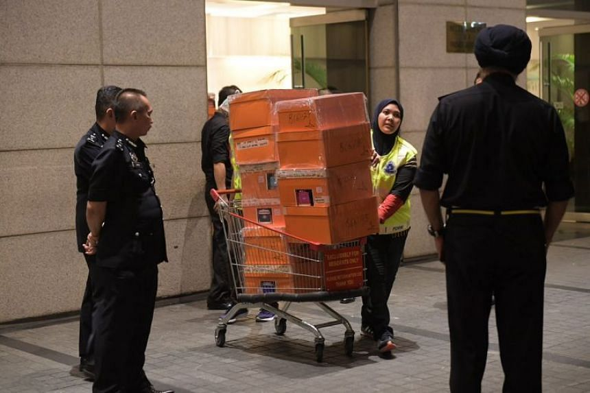 A police truck being loaded with orange boxes, the signature colour of the French luxury brand Hermes, following raids on three apartments belonging to former Malaysian prime minister Najib Razak.
