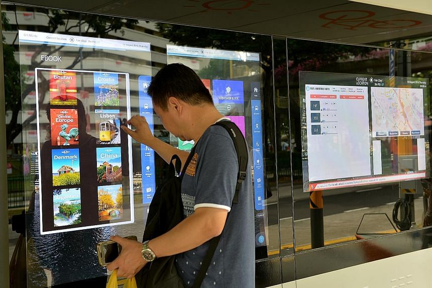 "A commuter checking out interactive ""smart boards"" at a bus stop. Such boards offer information such as bus timings, the weather and street directory. There are physical books to browse, as well as e-books to download too. Commuters can also use mobi"