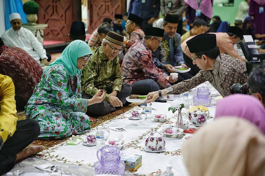 President Halimah Yacob, with her husband Mohamed Abdullah Alhabshee, taking a date offered by Muis president Mohammad Alami Musa during last night's iftar at An-Nahdhah mosque in Bishan.